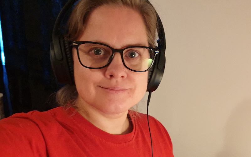 Photo of Elin with headphones, red t-shirt, in front of her computer. Photo: Mittens and Sunglasses © 2020