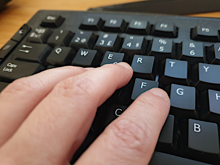 Fingers touching a black computer keyboard. Photo: Mittens and Sunglasses © 2021