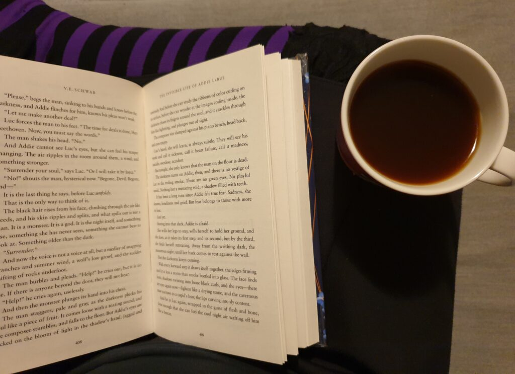 An open book on a lap of crossed legs, a cup of coffee balancing on the righ knee. Photo: Mittens and Sunglasses © 2021